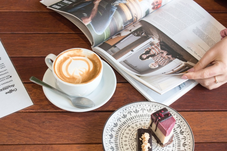 A woman with pink coloured nails, a pink crunchy on her wrist and a small gold ring on her ringer is reading a magazine. Next to the magazine on the wooden table is a coffee that has a coffee art design. On a plate next to the coffee is two small cake slices.