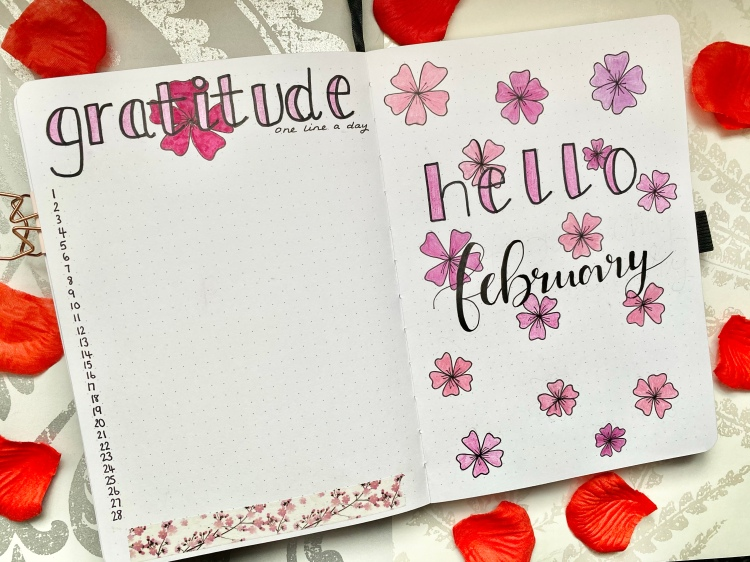 "This is a bullet journal spread. On the left page is a gratitude tacker, with the dates down the side of the page and ""gratitude"" is written in black ink coloured in pink with a big hot pink cherry blossom drawn behind the letters. The bullet journal is on multi floral paper with red rose petals around the journal."