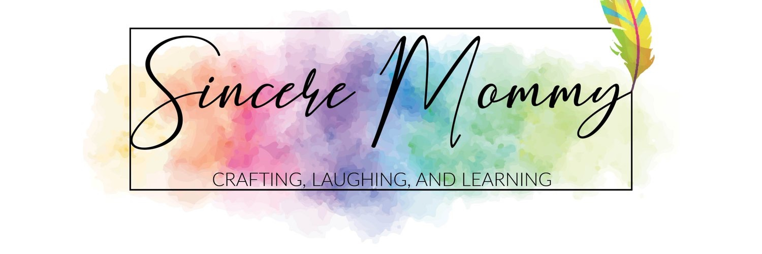 Sincere Mommy blog planner with a multi coloured feather and multicoloured paint splashes behind the text
