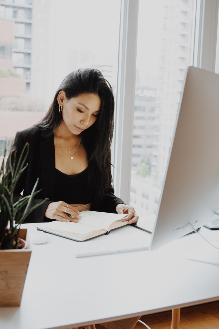 There is a woman with dark brown hair; she is wearing gold hoop earrings, gold necklaces and rings. She is sat at a white desk in front of a desktop screen and is working in a planner or notebook. On the desk is a plant in a wooden