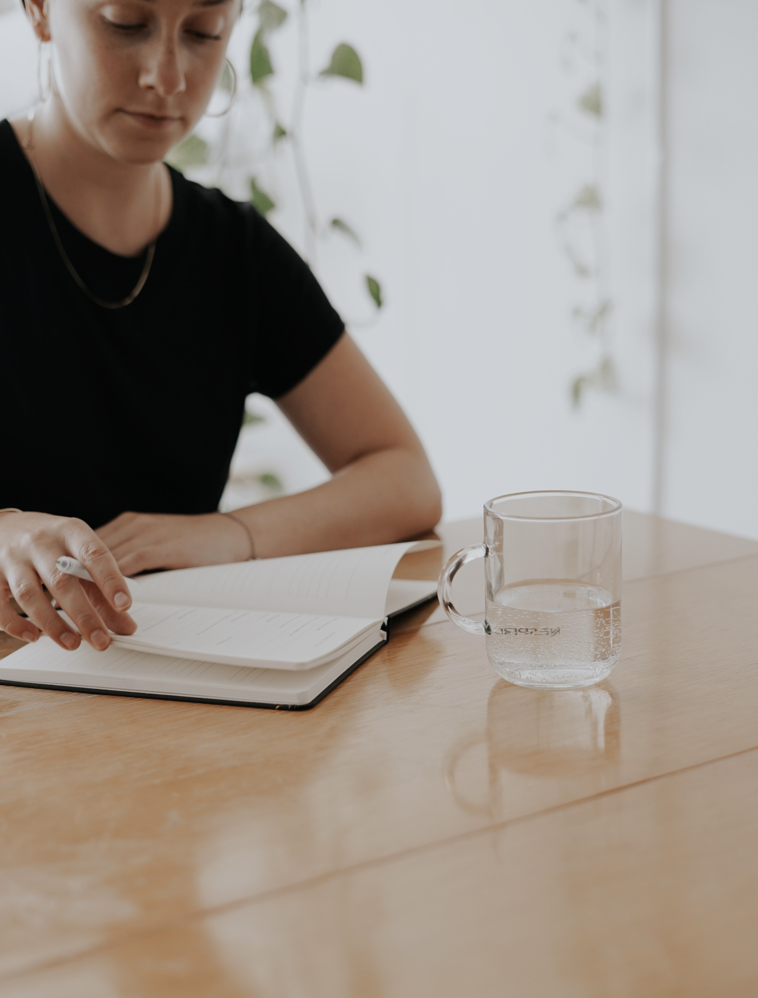 There is a woman in a black t-shirt who is sat at a table with a clear mud of water. She has a notebook open and is holding a pen.