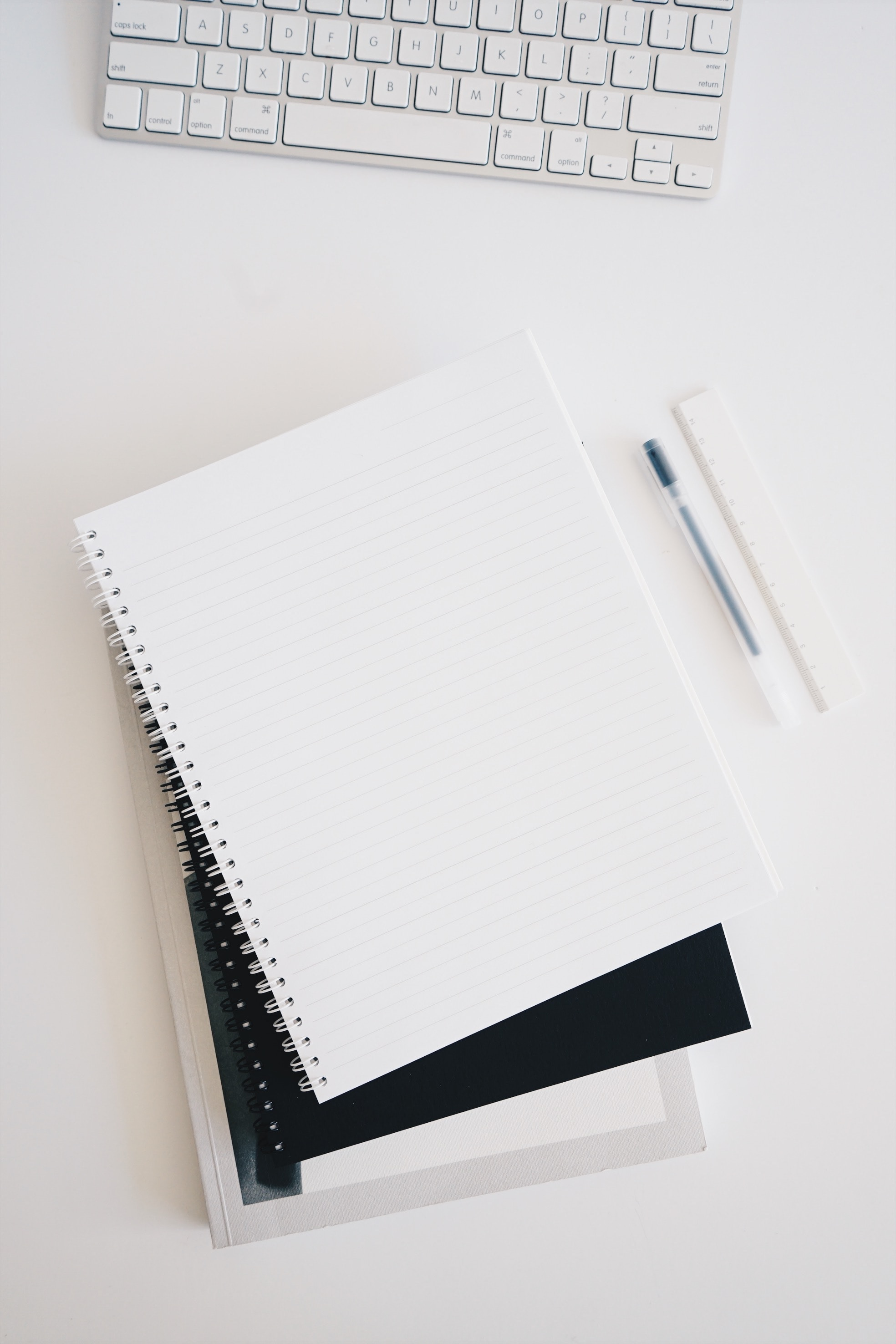 On a white work top is a white keyboard at the top of the picture. There is 3 notebooks, the notebook on the top is open with white lined pages. Next to the notebooks is a black pen and a white ruler.