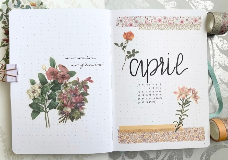 A double bullet journal page. On the left is two flower stickers with the quote no rain no flowers quote. On the right page is an April cover page with a mini calendar underneath and washi tape at the top and bottom of the page with flower stickers at the top and bottom.