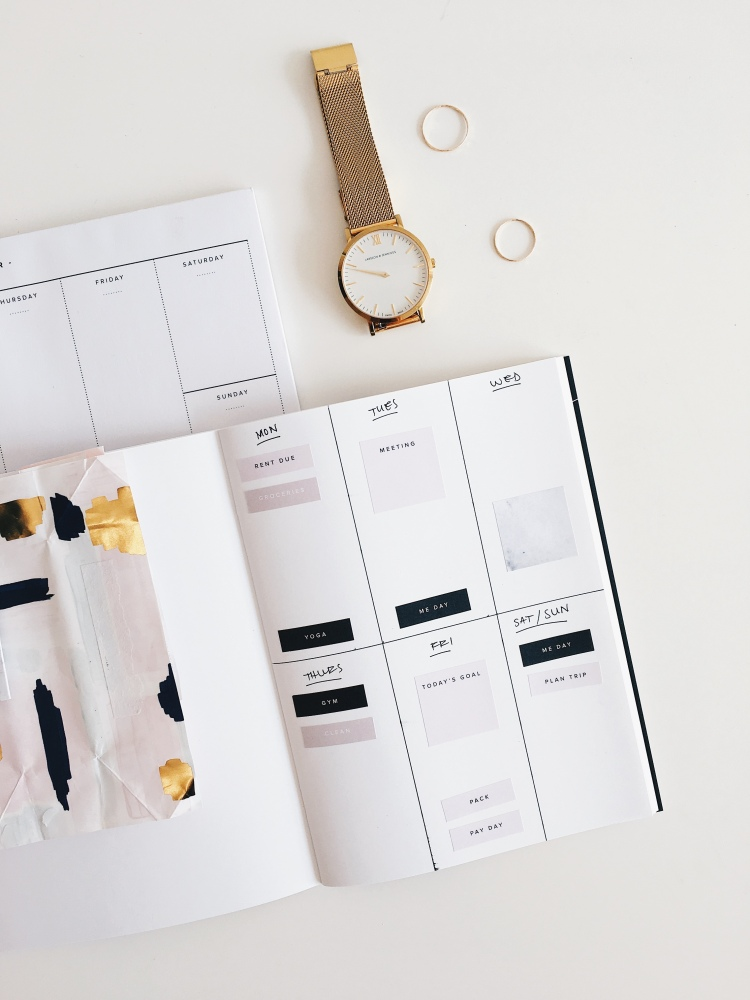 On a white work top is an opened notebook that has planner stickers on the left hand page, on the right page is a weekly spread. Next to the bullet journal is a gold watch and two gold rings.