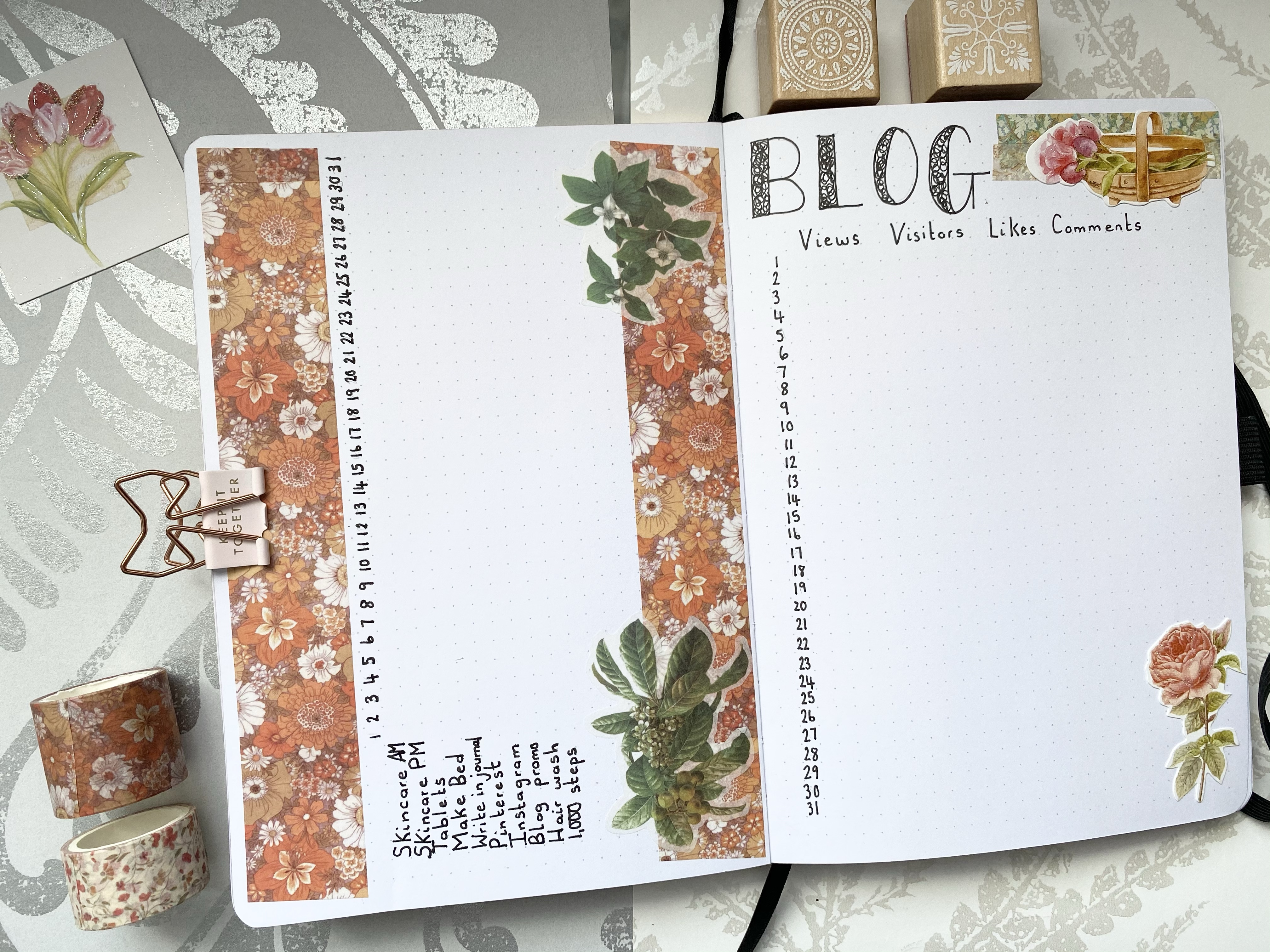 A bullet journal double page spread. On the left page is a habit tracker with thick orange floral washi tape and green flower stickers. On the right page is a blog statistics page that has green floral washi and flower stickers and one with a brown basket of flowers. There is washi tape next to the left side of the bullet journal and wooden stamps on the top right page of the bullet journal.