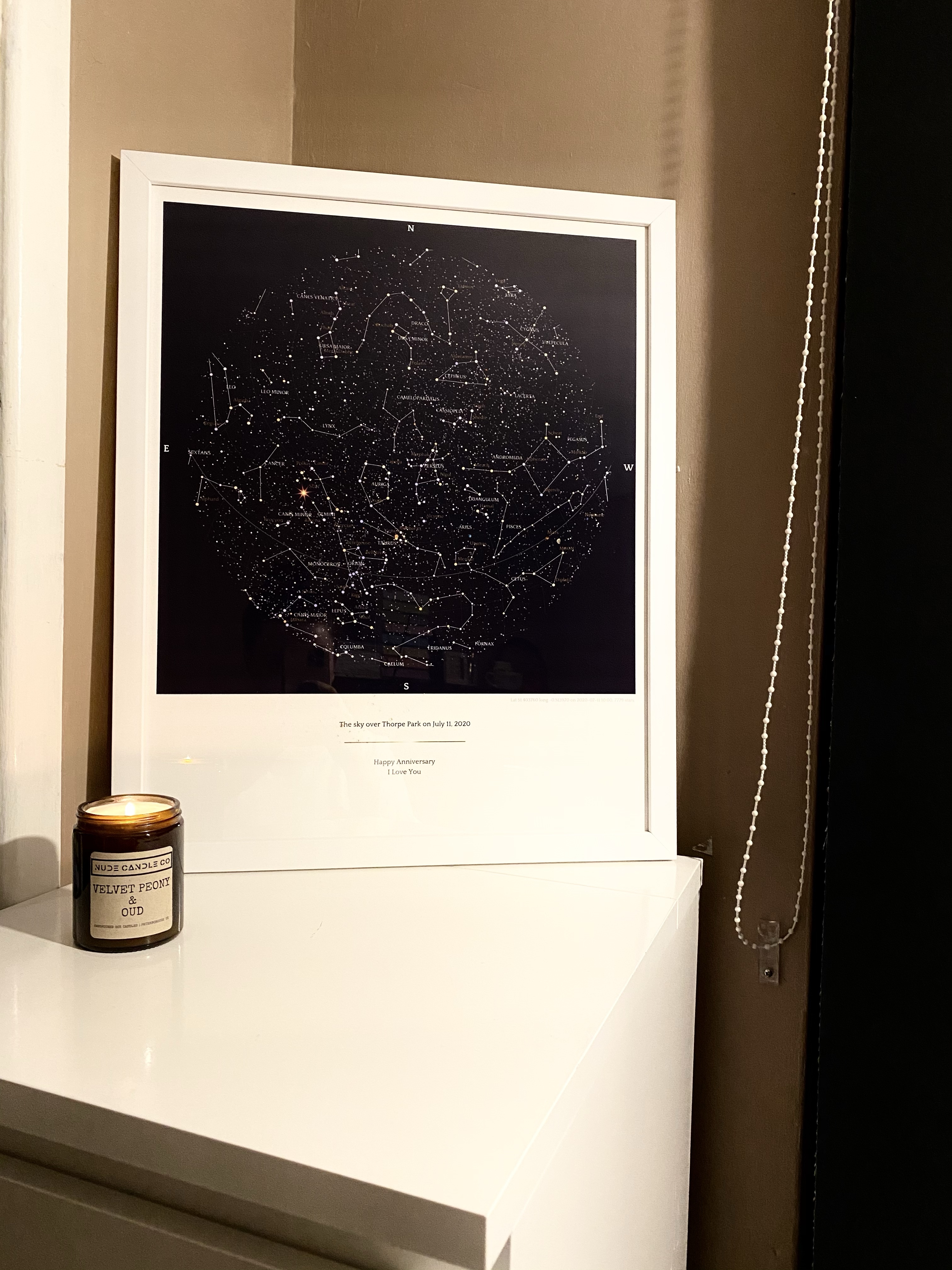 A Greater Skies Map that is in navy and in a white frame. This print has a map with a white, gold and silver detail.