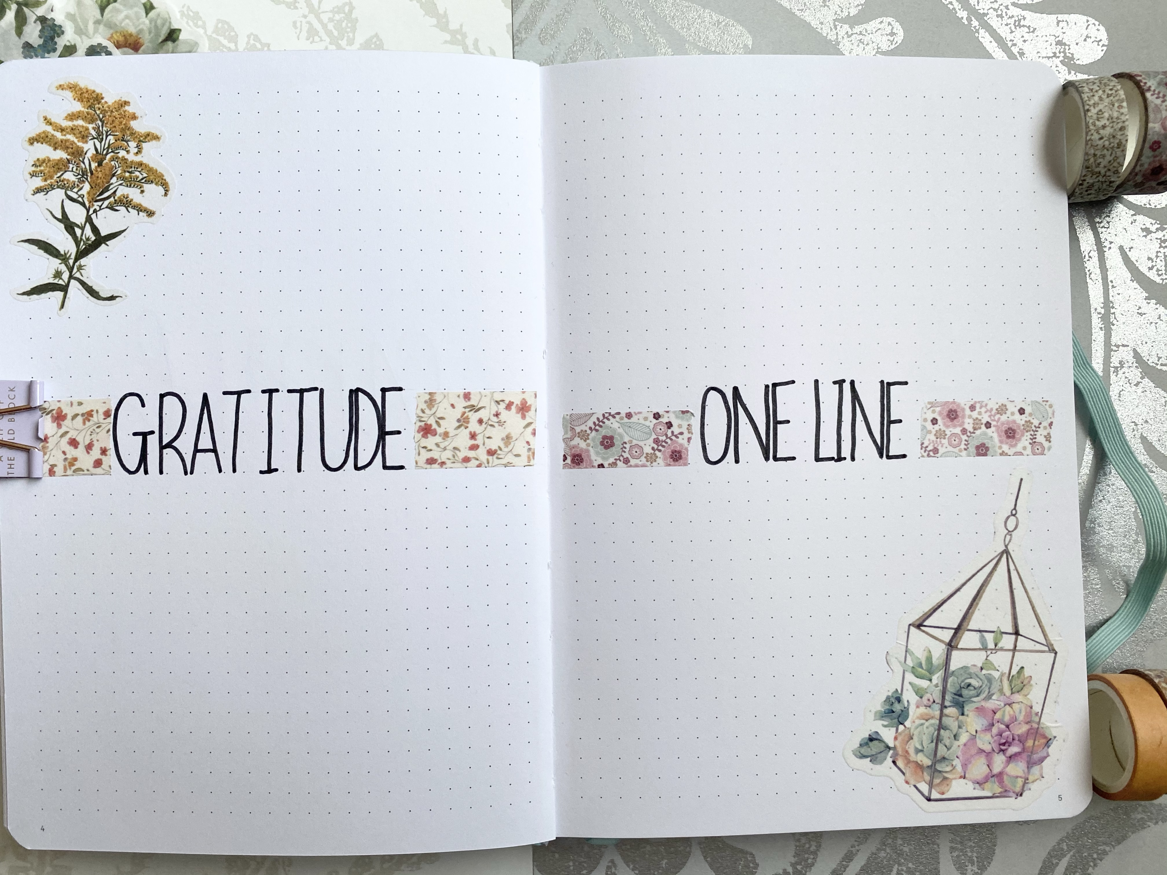 A bullet journal double page spread. On the left side page is gratitude written in the middle with floral washi tape either side with a floral sticker in the left hand corner. On the right page is one line in the middle with floral washi tape either side and a floral sticker in the right bottom hand corner.