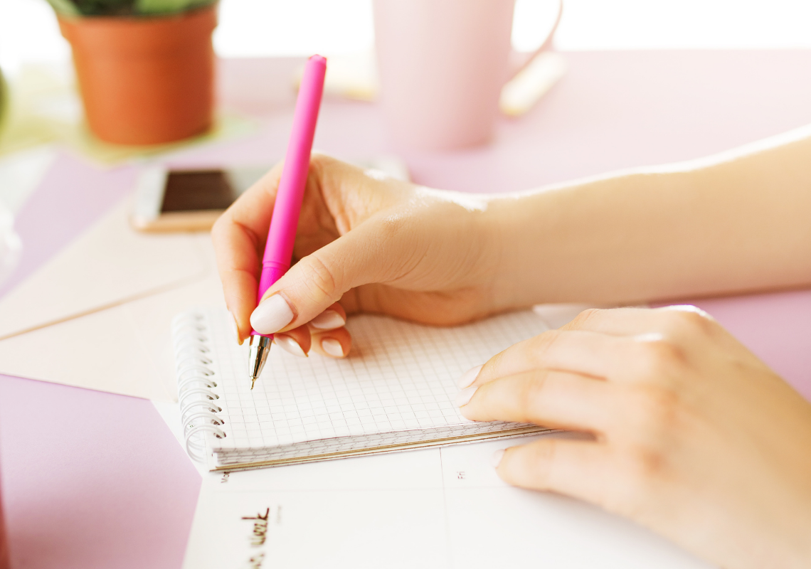 A white desk with a woman writing in a squared notebook. Holding a pink pen. An iPhone and plant in the background.