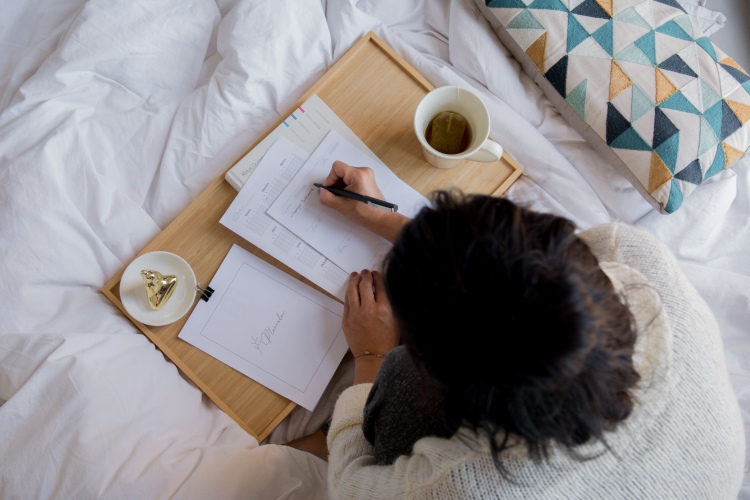A person writing on paper and planning. They are sat on a white bed spread with a light coloured wooden tray with a tea next to them.