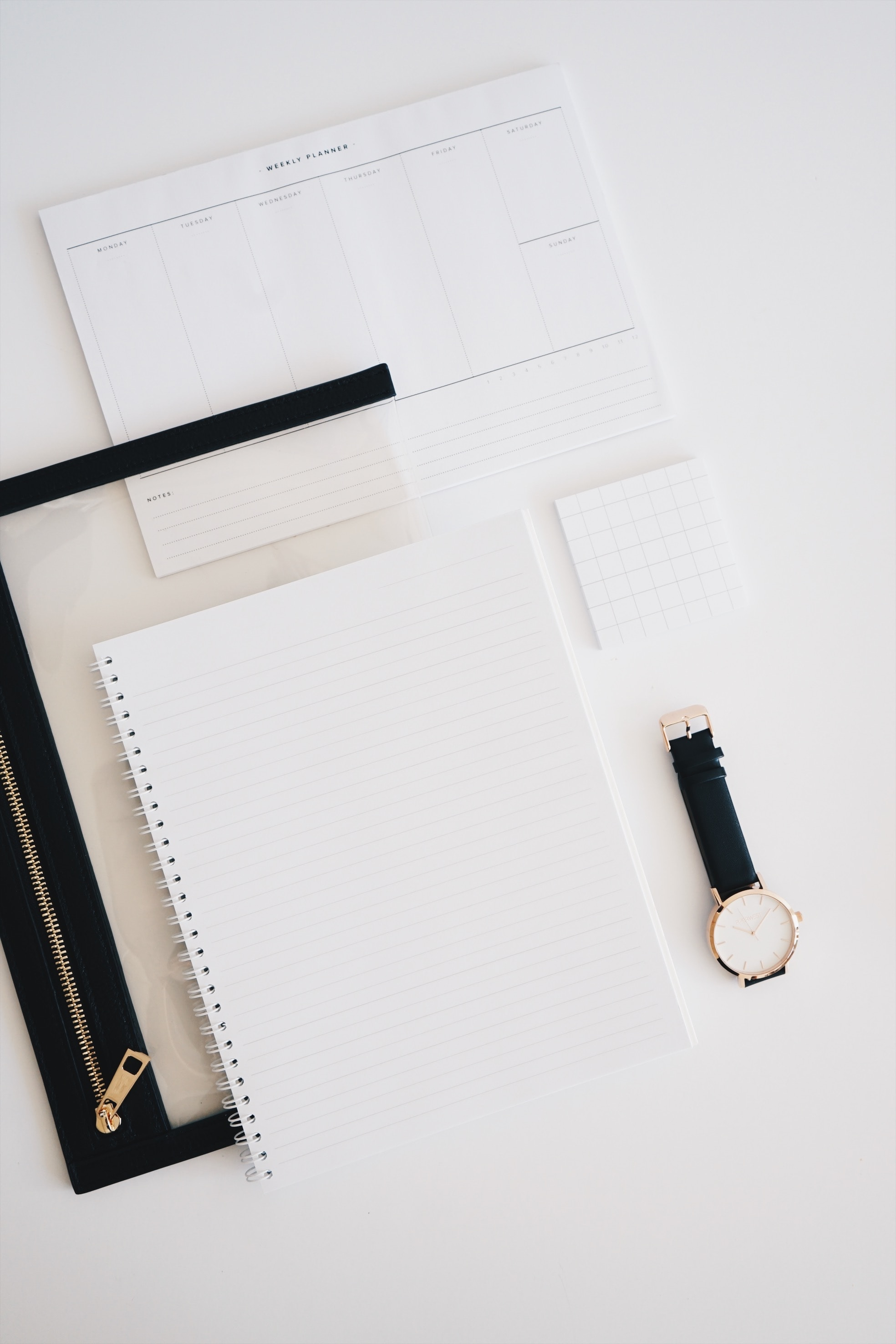 A lined A4 notebook, with a black wrist watch and a weekly planner.