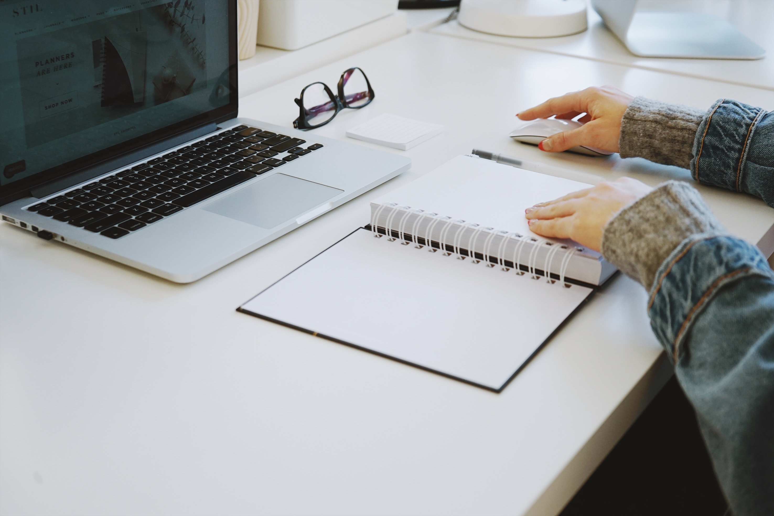 A woman sat at a white desk with an open notebook/planner using a macbook pro and an apple mouse. On the desk there is a small white pad and a pair of dark rimmed glasses