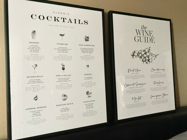 Two posters in black frames. The poster on the left is a cocktail guide and the other is a wine guide.