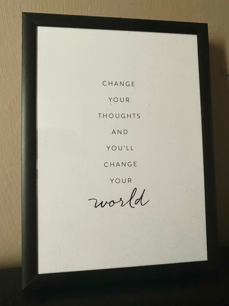 """A small poster in black frame that says """"Change your thoughts and you'll change your world""""."""