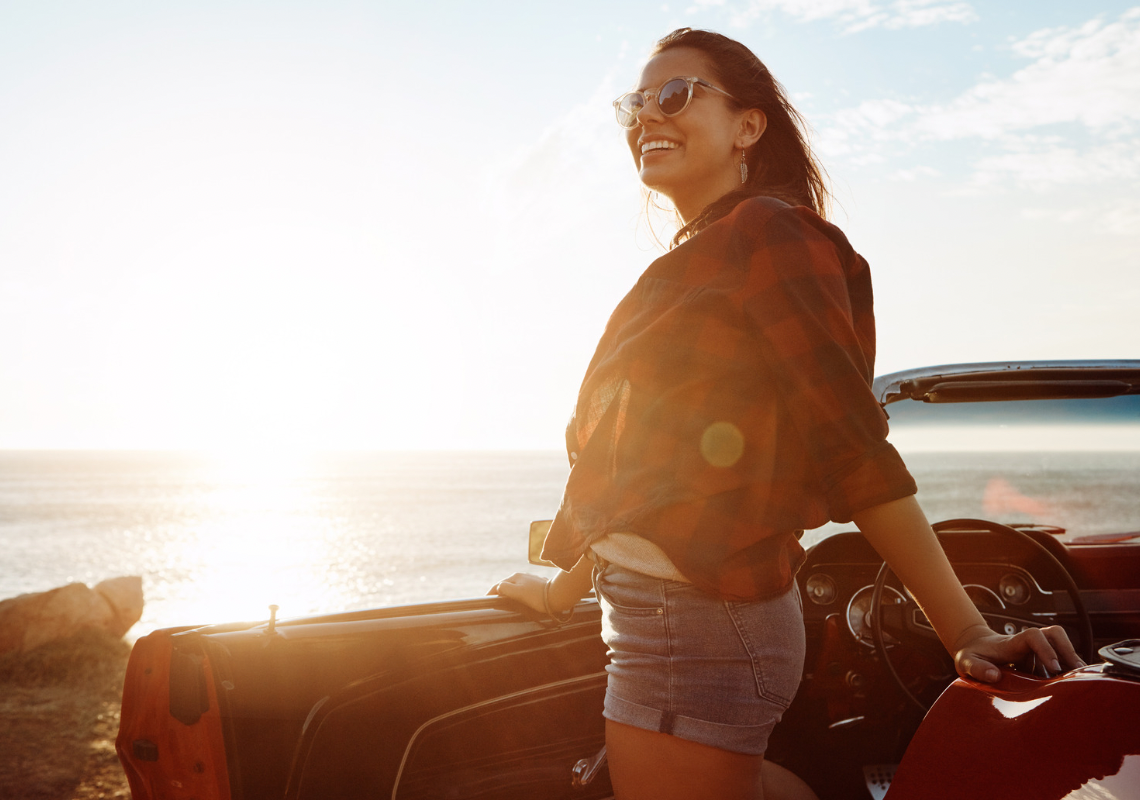 A brown haired lady getting out of a convertible car by the beach smiling on a sunny day