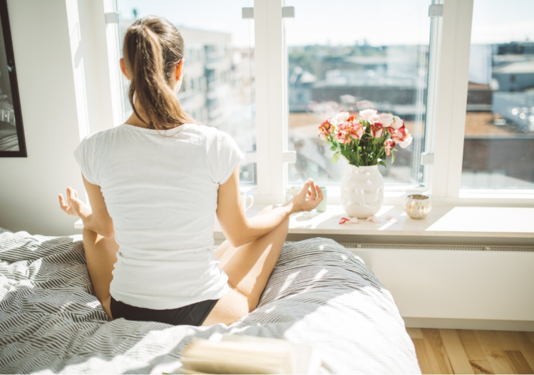 A woman sat on the bed meditating next to the window