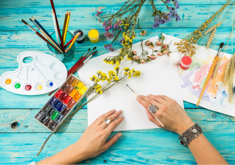A person is painting on white paper with flowers next to the paper