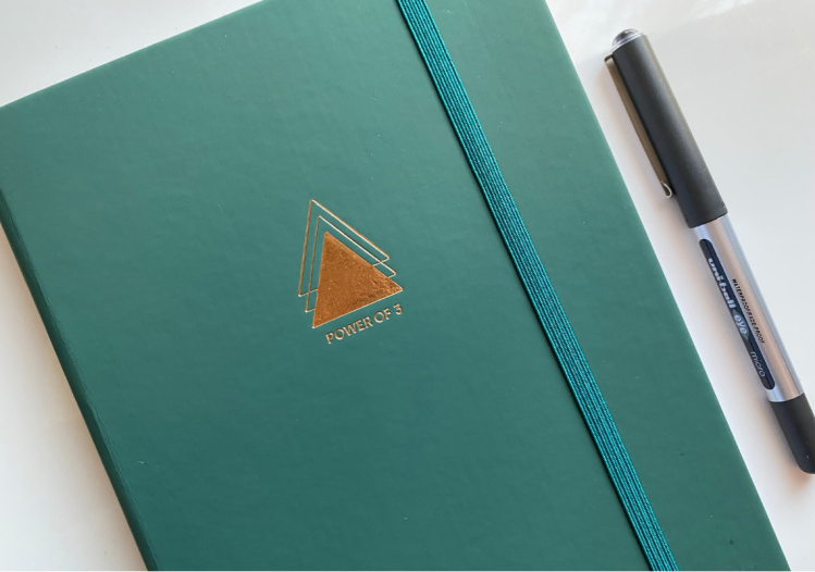 Forest green goal planner notebook with a gold triangle on the front and power of 3 written in gold