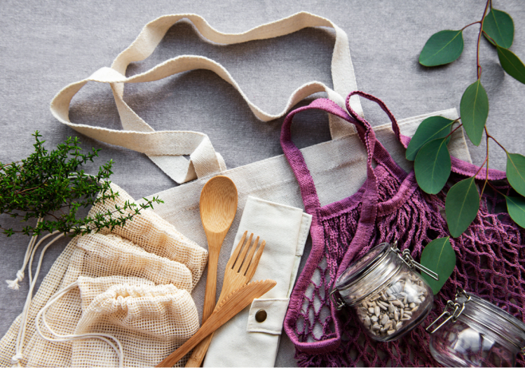 A white and purple reusable bag with wooden cutlery and loose leaves