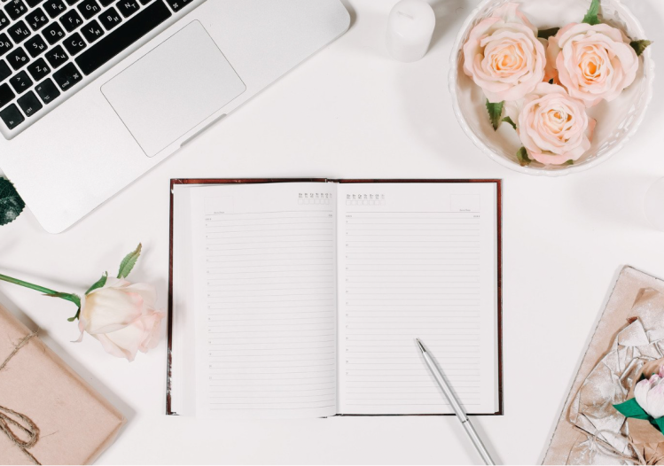 A planner open on a desk with a silver laptop with faux flowers and a pen