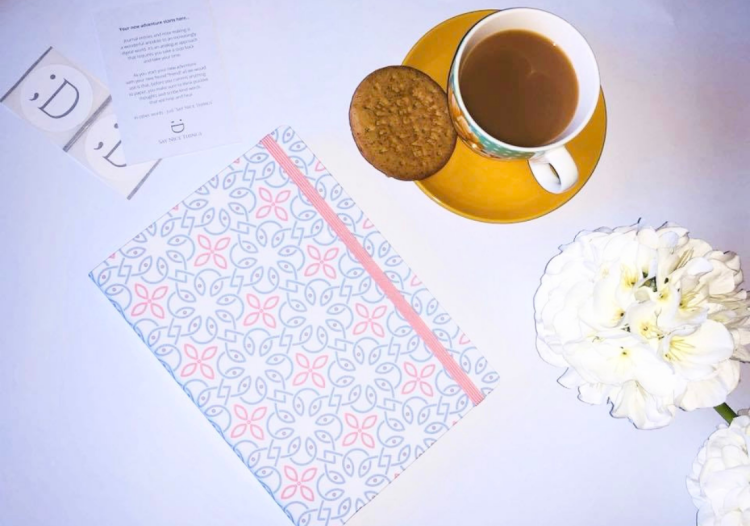 A notebook with a peach and blue pattern with fairy lights, with faux plants and stickers