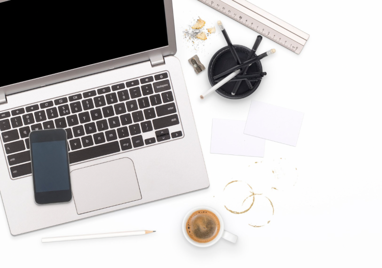 A white desk with a silver laptop to the left which has a phone, a mug of coffee and some stationery
