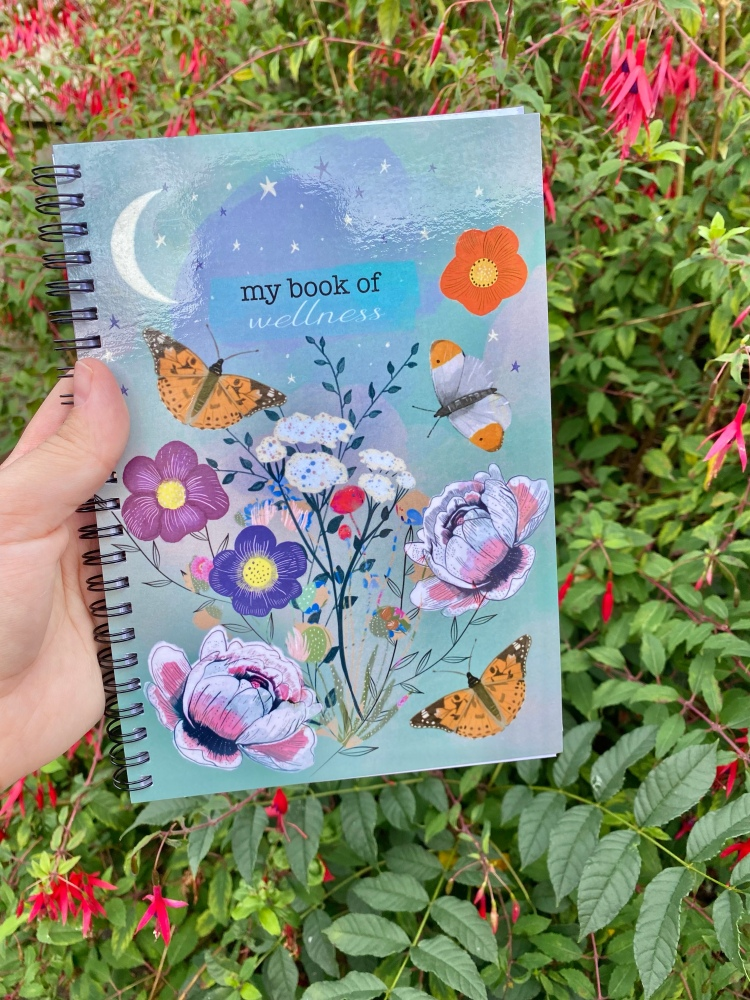 A notebook that says my book of wellness. The notebook has hand designed butterflies, flowers and the environment. Behind the notebook is a flower and leaf background.