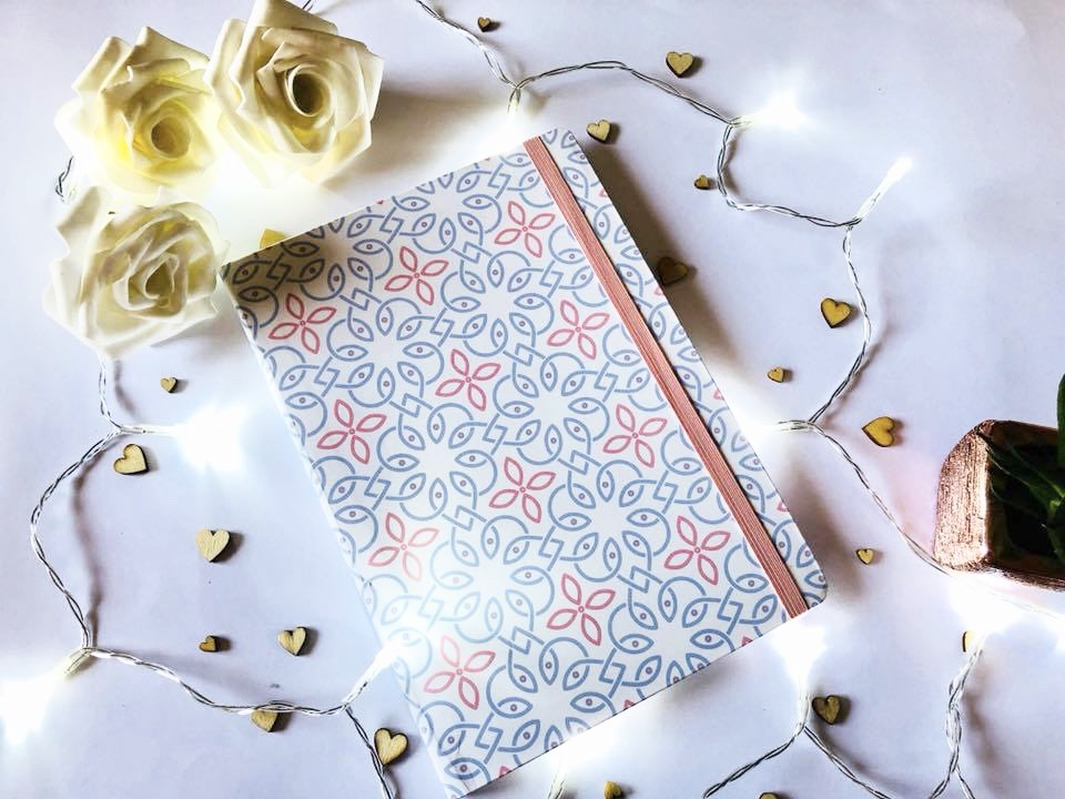 A peach and blue patterned journal with faux roses and fairy lights