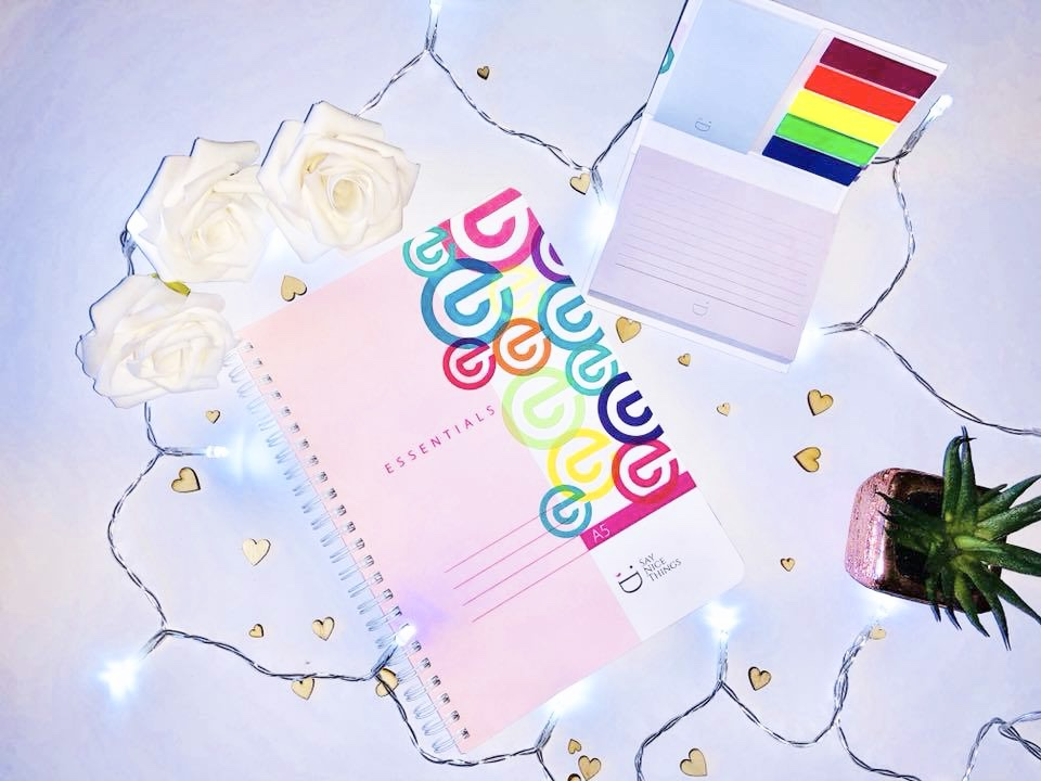 A pink notebook and sticky note tabs for studying around fairy lights