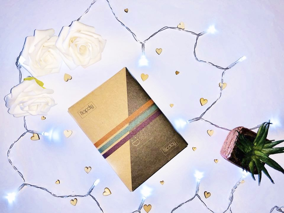 A flip notebook with fairy lights, faux roses and little wooden hearts